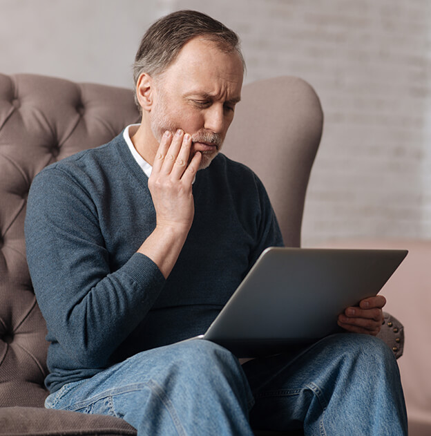 man holding his jaw in pain while looking at his laptop