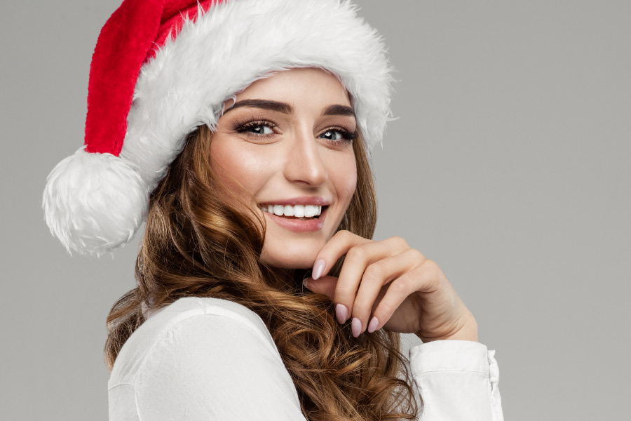 Brunette woman smiles while wearing a red Santa hat for the holidays