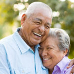 senior couple hug and smile after learning about the benefits of dentures